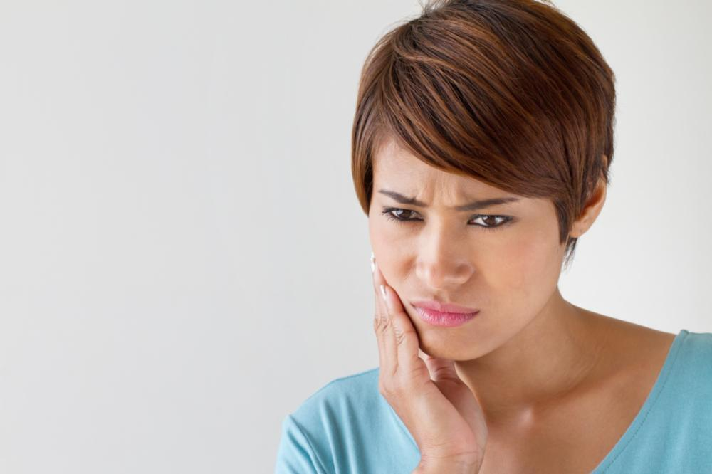 woman holding jaw | dental emergency santa monica