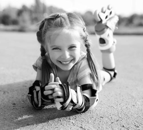 Little girl smiling with roller blades on