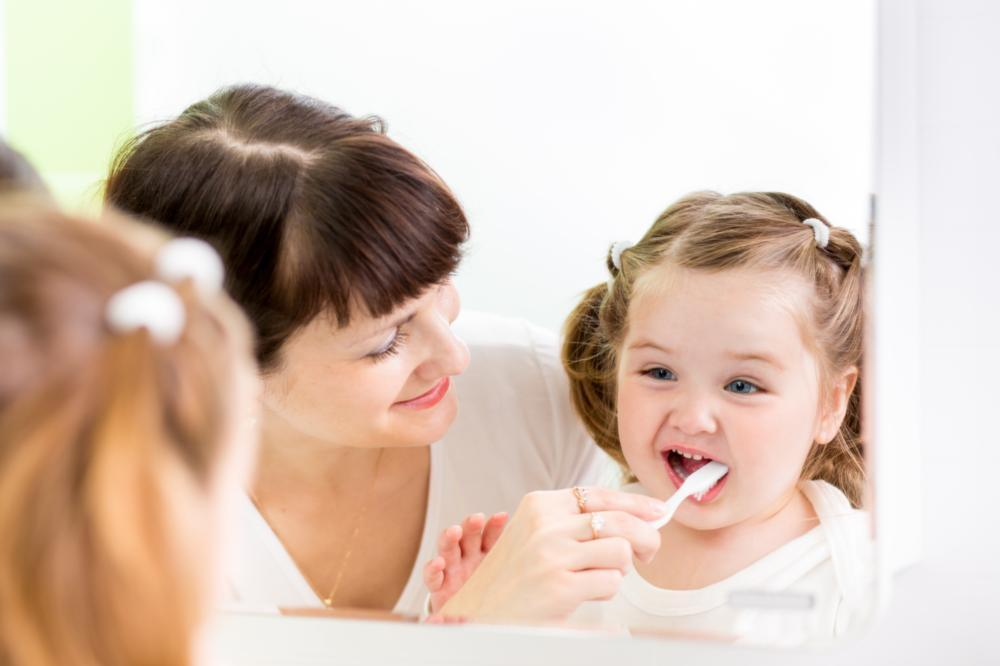 mom helping daughter brush teeth