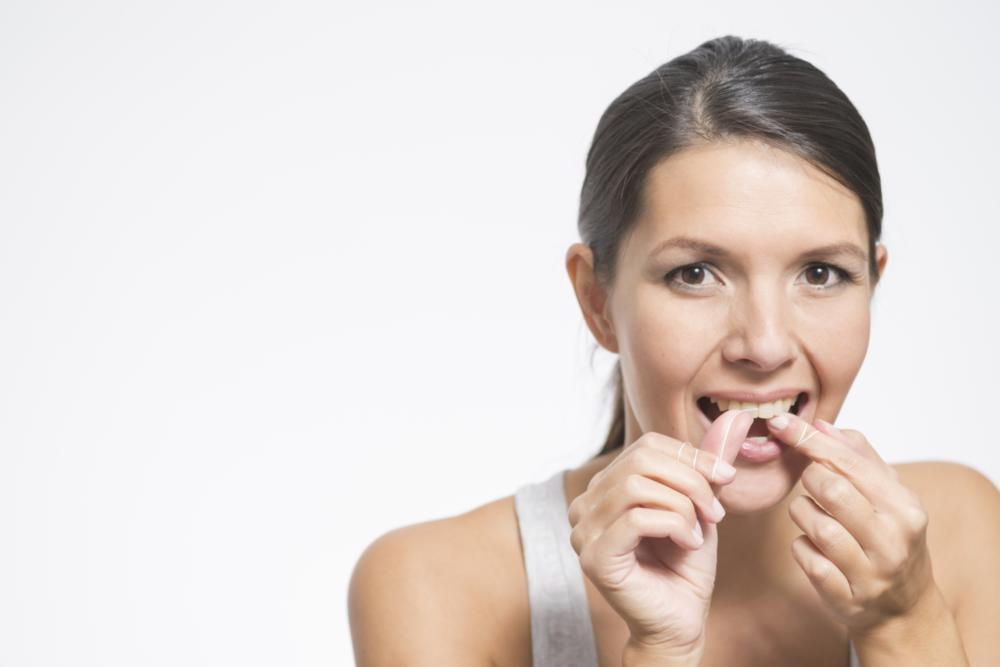woman flossing teeth | dentist santa monica ca