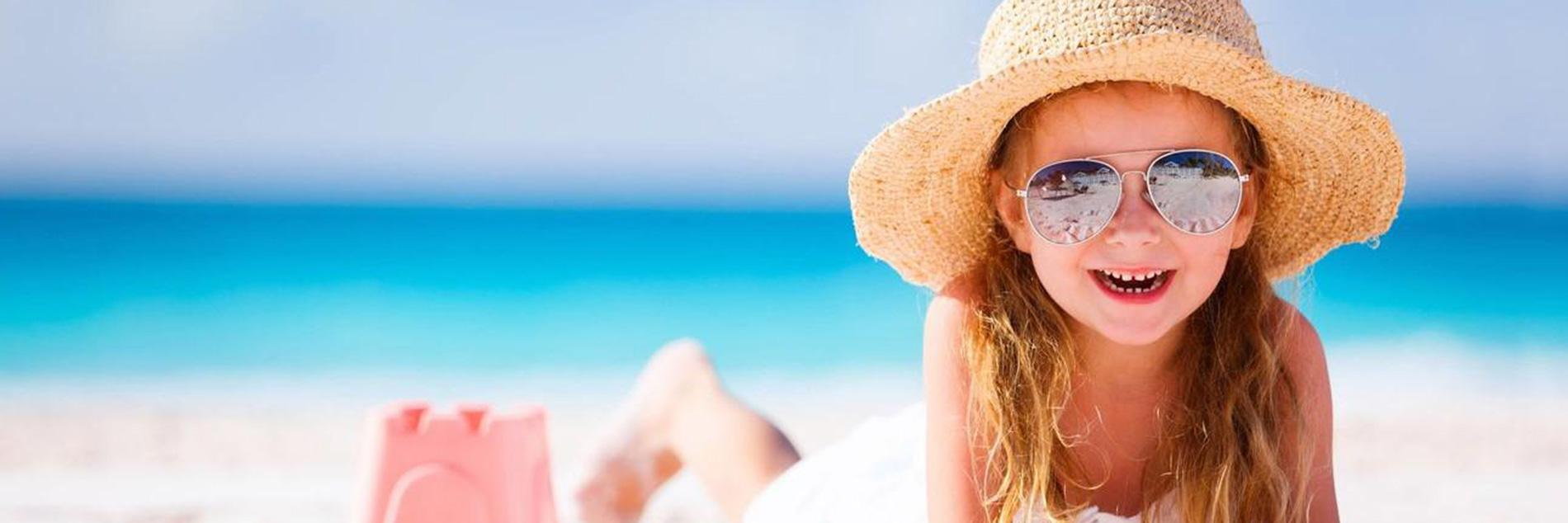 Girl on Beach with sun glasses and sun hat
